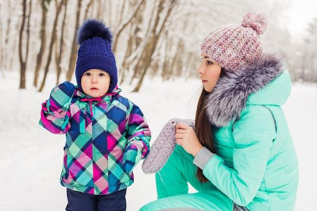 Klein meisje en haar moeder hebben plezier op een winterdag.