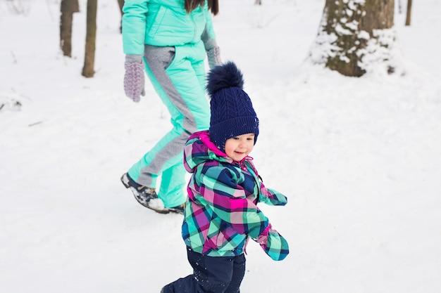 Klein meisje en haar moeder hebben plezier op een winterdag. Premium Foto