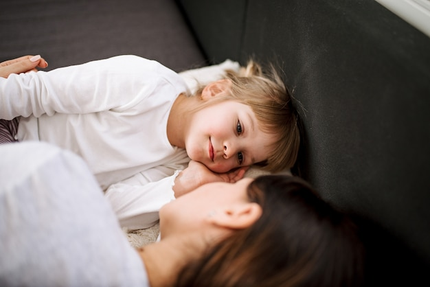 Klein meisje en haar moeder in bed liggen.