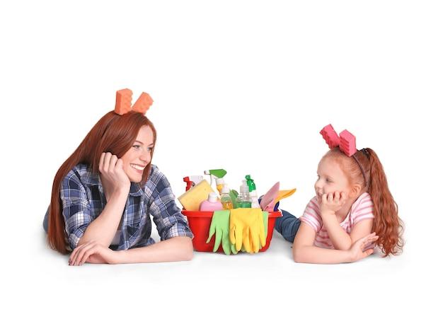 Klein meisje en haar moeder met schoonmaakproducten op witte achtergrond