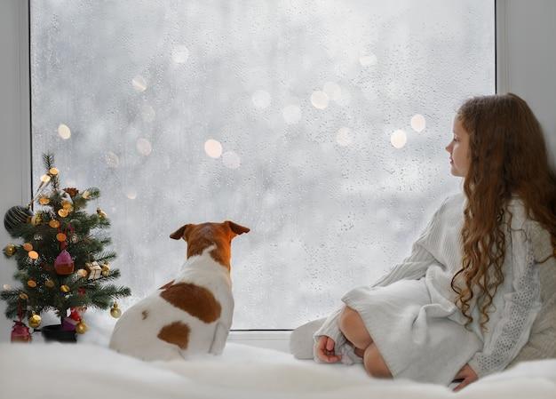 Klein meisje en haar puppy jack russell zitten bij het raam