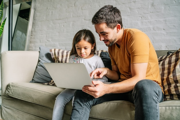 Klein meisje en haar vader met behulp van een laptop samen thuis.