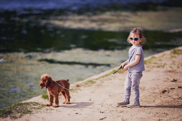 Klein meisje en hond op het strand in zonnige zomerdag kind met puppy buitenshuis