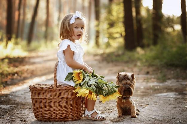 Klein meisje en hond zitten in de natuur met een boeket bloemen