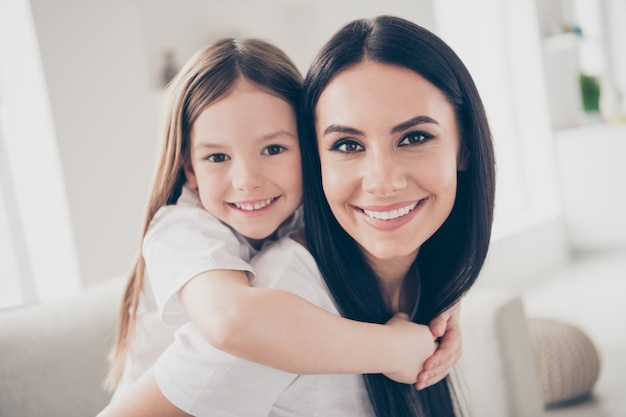 Klein meisje en jonge moeder knuffelen meeliften in huis huis binnenshuis