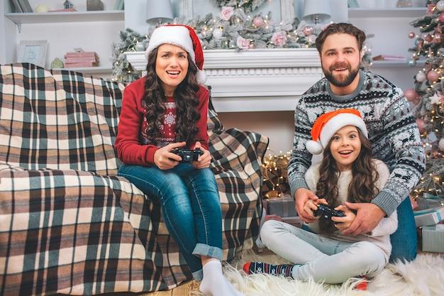 Klein meisje en jonge vrouw speelspel met behulp van joysticks. vader helpt zijn dochter. zij hebben lol. het gezin is geconcentreerd.