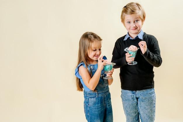 Klein meisje en jongen eten ijs op een lichte achtergrond