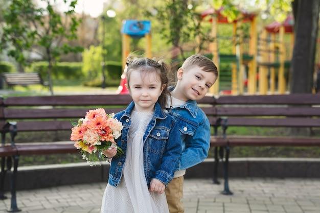 Klein meisje en jongen in het park met een boeket bloemen