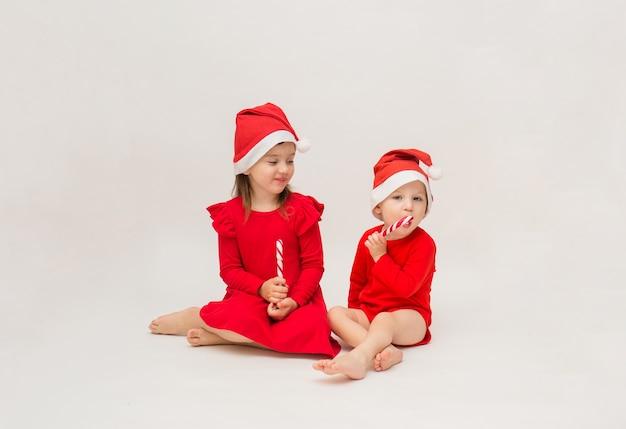 Klein meisje en jongen in rode kappen met lollies op een witte muur met een kopie van de ruimte