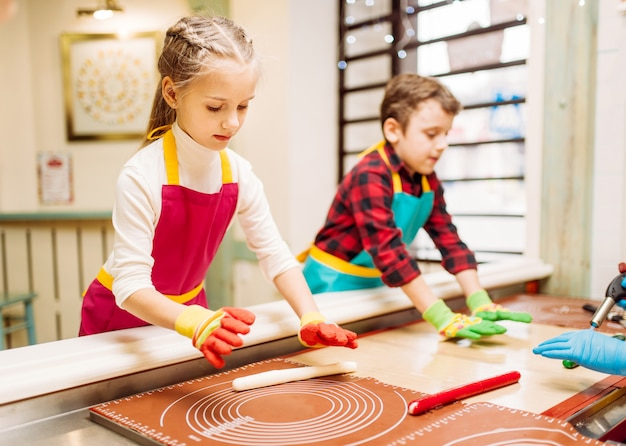 Klein meisje en jongen in werkplaats bij patisserie leren karamel te maken. vakantieplezier in de snoepwinkel. lolly voorbereidingsproces