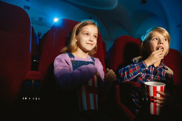 Klein meisje en jongen kijken naar een film in een bioscoop