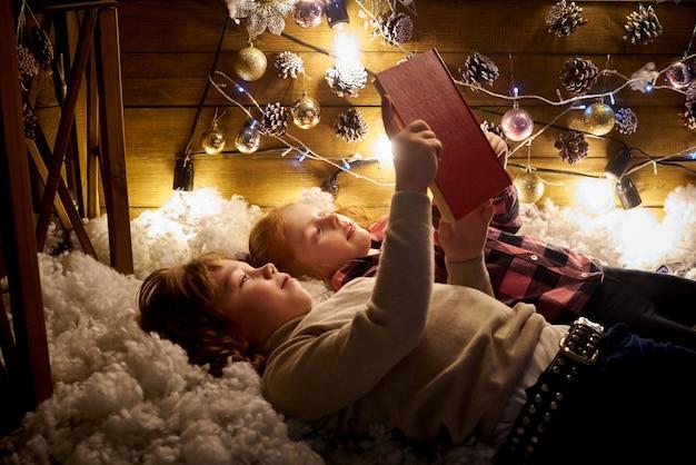 Klein meisje en jongen lezen een boek in een ingerichte kamer voor kerstmis.