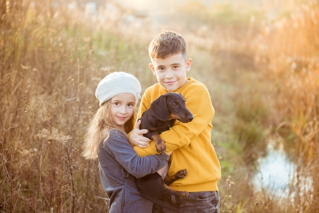 Klein meisje en jongen met hond die natuurvakantie verkennen. kinderen met hond wandelen langs de natuur, herfst