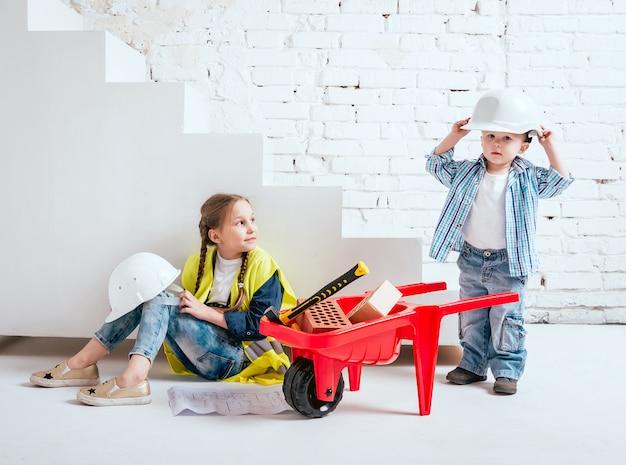 Klein meisje en jongen met kruiwagen op het witte landschap. bouw