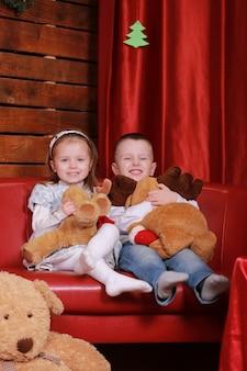 Klein meisje en jongen op bank in kerststudio in rode kleuren. kerstboom en teddybeer op de muur.