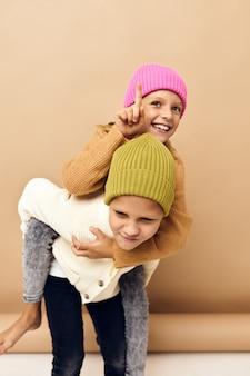 Klein meisje en jongen samen in veelkleurige hoeden leuke vrijetijdskleding studio levensstijl