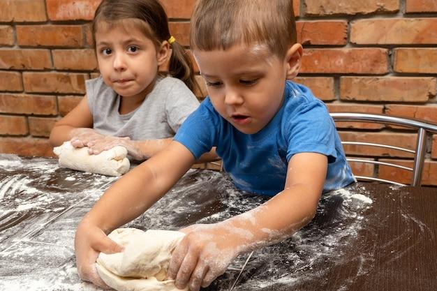 Klein meisje en jongensdeeg voor kinderen, deeg voorbereiden om te bakken
