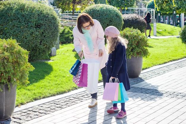 Klein meisje en moeder blij en kijken naar aankopen in boodschappentassen.