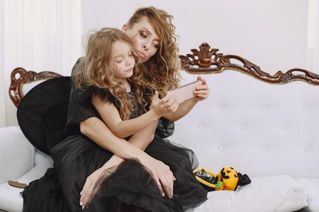 Klein meisje en moeder dragen zwarte jurken