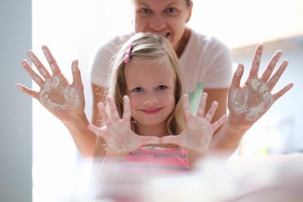 Klein meisje en moeder tonen hun handpalmen besmeurd met bloem en glimlachen
