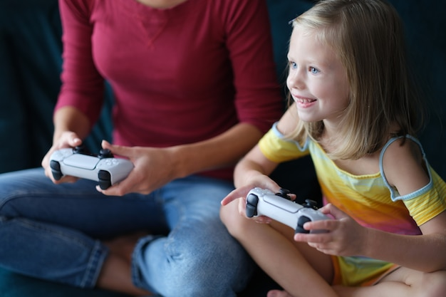 Klein meisje en moeder zitten op de bank en houden computerjoysticks in hun handen