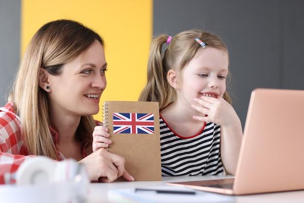 Klein meisje en moeder zitten voor laptop met engelse studieboeken
