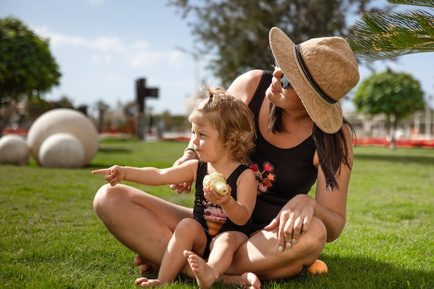 Klein meisje en moeders in de zomer op het gras tussen de palmen