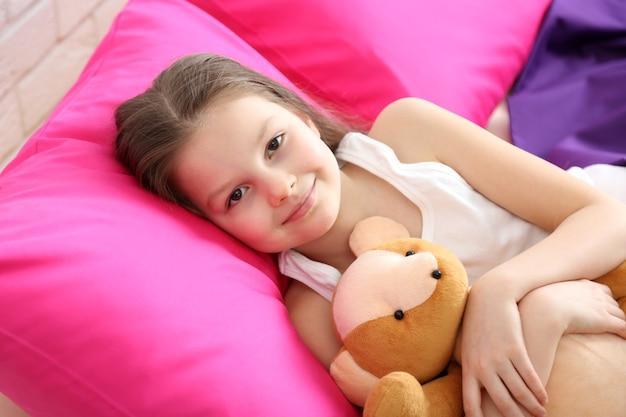 Klein meisje en speelgoed beer in bed