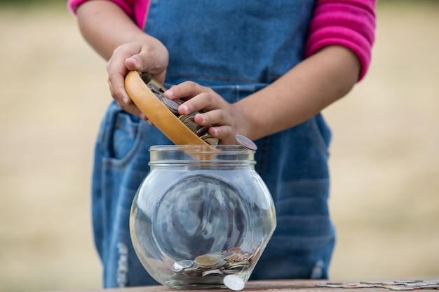 Klein meisje en stapel munt voor het opslaan. geld besparen concept.