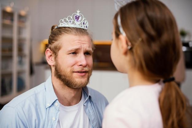 Klein meisje en vader spelen met tiara
