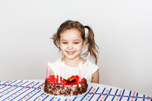 Klein meisje en verjaardagstaart, blaast kaarsjes uit, doet een wens, taart en kaarsjes, verjaardagscadeautjes, familie, mama en papa