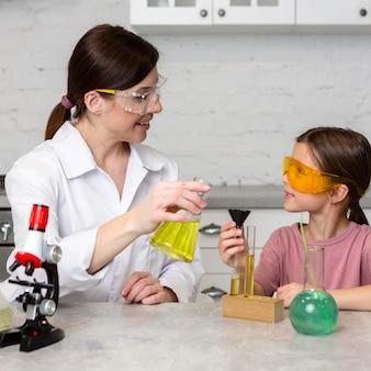 Klein meisje en vrouwelijke leraar doen wetenschappelijke experimenten met reageerbuizen