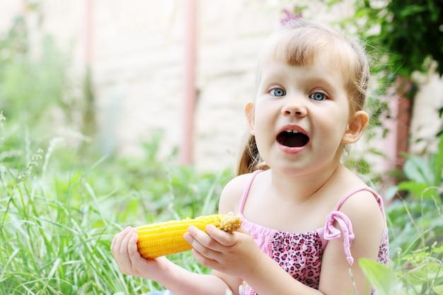 Klein meisje eten van maïs