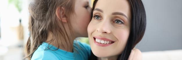 Klein meisje fluistert geheim in moederoor