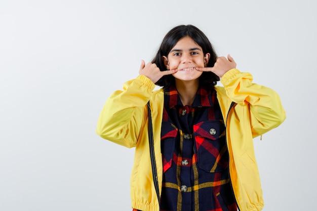 Klein meisje fluitend met vingers in geruit overhemd, jasje en ziet er mooi uit. vooraanzicht.