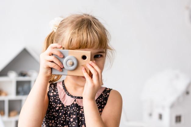 Klein meisje foto met speelgoed fotocamera binnenshuis maken