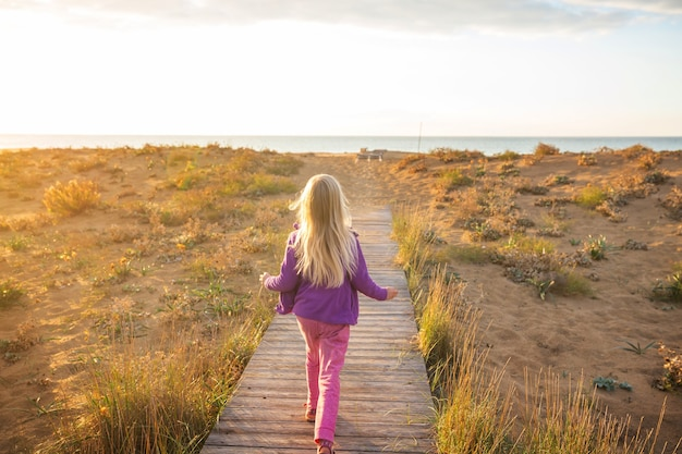 Klein meisje gaat bij zonsopgang over de promenade in de kust