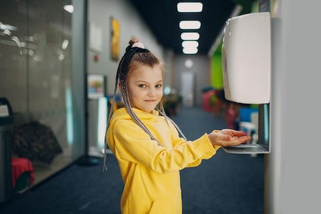 Klein meisje gebruikt automatisch ontsmettingsmiddel met alcoholgeldispenser voor antiseptische handen
