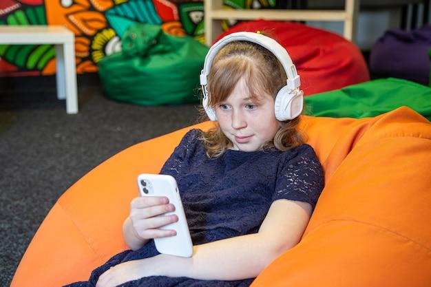 Klein meisje gebruikt de telefoon en luistert naar muziek met een koptelefoon terwijl ze op de stoel van de tas zit