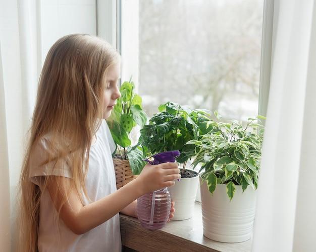 Klein meisje geeft kamerplanten water in haar huis