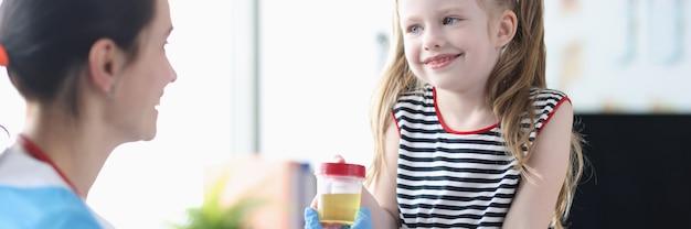 Klein meisje geeft pot urine aan verpleegster in kliniek