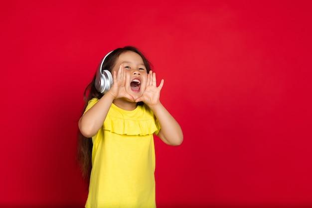 Klein meisje geïsoleerd op rood, happy