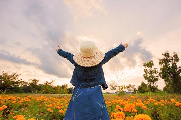 Klein meisje gekleed in een bloementuin.