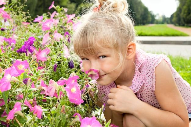 Klein meisje geniet van de geur van bloemen