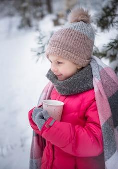 Klein meisje gewikkeld in een deken die thee drinkt in het winterbos