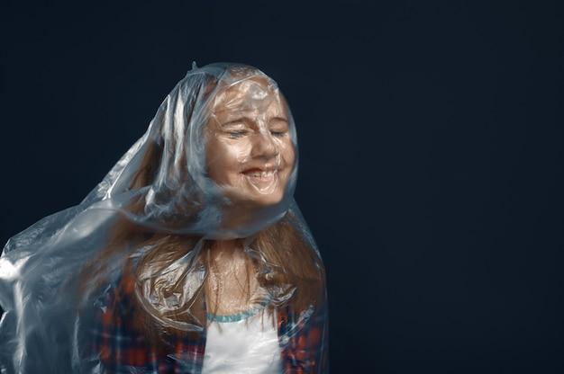 Klein meisje gewikkeld in film die tegen krachtige luchtstroom staat