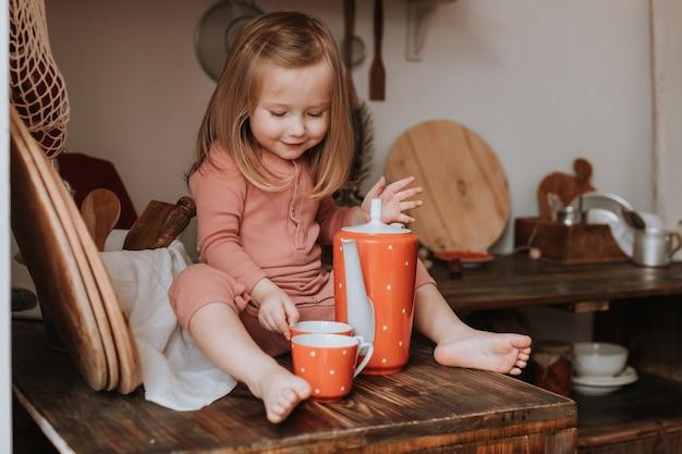 Klein meisje giet thee in een mok uit een theepot rode keramische gerechten in witte erwten houten keuken