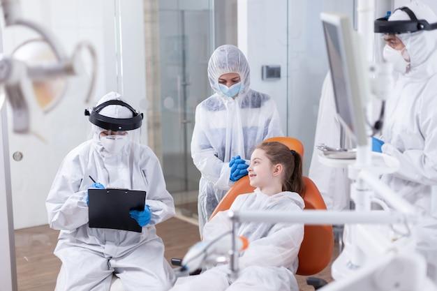 Klein meisje glimlachend bij pediatrische tandarts zittend op tandartsstoel in de loop van tandheelkunde check-up. stomatoloog tijdens covid19 die een ppe-pak draagt en een tandenprocedure uitvoert van een kind dat op een stoel zit.