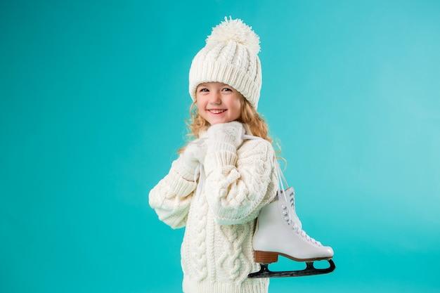 Klein meisje glimlachend in een winter witte hoed en trui, met schaatsen