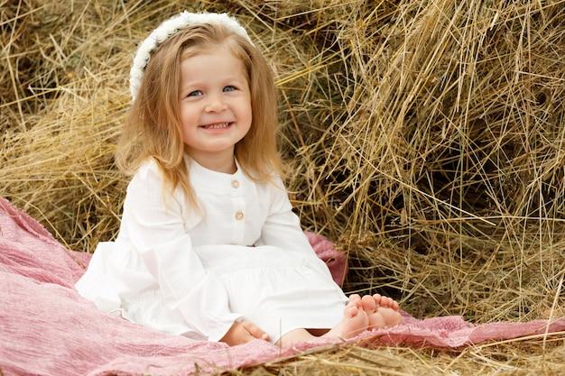 Klein meisje glimlachend in een witte jurk op het hooi